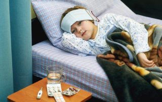 Complications Fever: feverish child sick in bed treated with cold wraps, hot drinks and medication