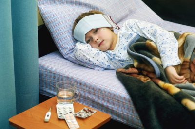 feverish child sick in bed treated with cold wraps, hot drinks and medication