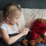 Ein Kind heilt seinen Teddybaer mit der richtigen Medizin gegen Fieber.
