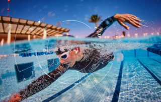 An athlete swimming in a pool wearing the cosinuss° One